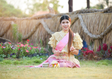 Foto de Asia woman thai style dress / Portrait of beautiful young girl smiling Thailand traditional costume wearing with thai jasmine garland in hand - Imagen libre de derechos