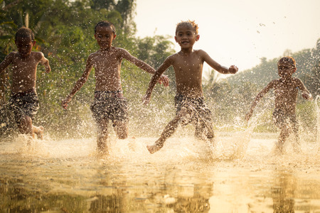 Foto de Asia children on river / The boy friend happy funny playing running in the water in countryside of living life kids farmer rural people - Imagen libre de derechos