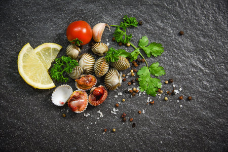 Foto de Shellfish Seafood Cockles fresh raw ocean gourmet dinner with herbs and spices on dark background - blood cockle peeled - Imagen libre de derechos