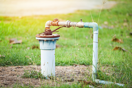 Foto de Groundwater well with pvc pipe and system electric deep well submersible pump water on green meadow - Imagen libre de derechos