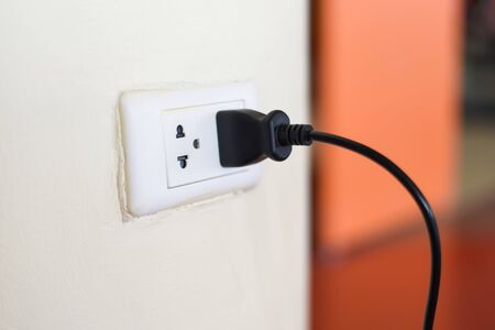 Foto de Home outlet plug is plugging socket on wall with black power cord cable / Power plug connecting electrical plug - Imagen libre de derechos