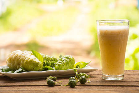 Photo for Noni and noni juice on wooden background.Juice for health or fruit for health or herb for health.Outdoor view - Royalty Free Image