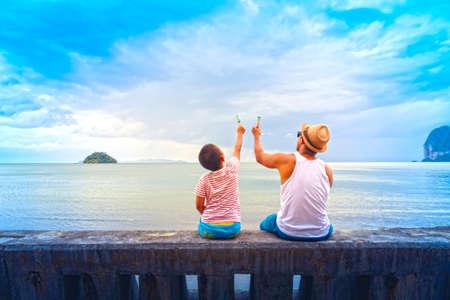 Foto de Father and son   eat ice cream Or Family Asian holding ice cream on the beach. - Imagen libre de derechos