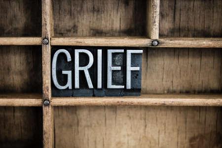 Foto de The word GRIEF written in vintage metal letterpress type in a wooden drawer with dividers. - Imagen libre de derechos