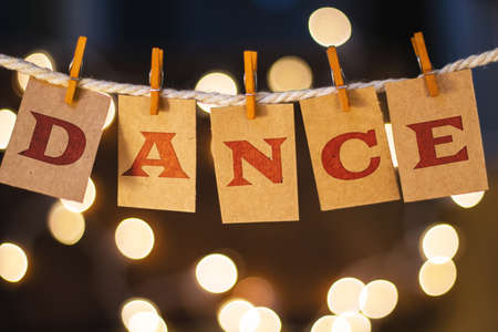 Photo for The word DANCE printed on clothespin clipped cards in front of defocused glowing lights. - Royalty Free Image