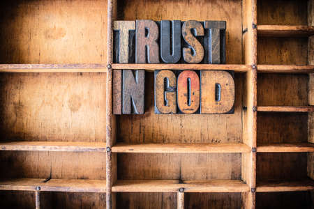 Photo pour The words TRUST IN GOD written in vintage wooden letterpress type in a wooden type drawer. - image libre de droit