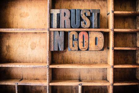 Foto de The words TRUST IN GOD written in vintage wooden letterpress type in a wooden type drawer. - Imagen libre de derechos