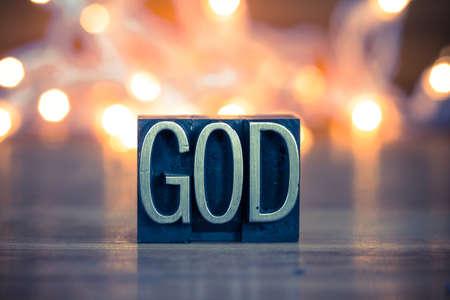 Foto de The word GOD written in vintage metal letterpress type on a soft backlit background. - Imagen libre de derechos