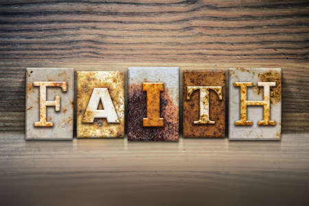Photo pour The word FAITH written in rusty metal letterpress type sitting on a wooden ledge background. - image libre de droit