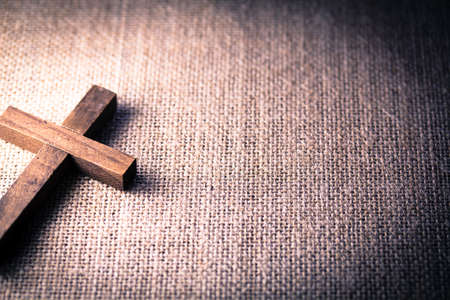 Photo for An aerial view of a holy wooden Christian cross on a burlap background. - Royalty Free Image