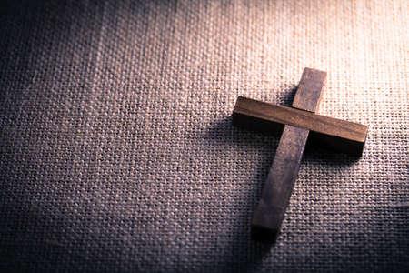 Photo pour An aerial view of a holy wooden Christian cross on a burlap background. - image libre de droit