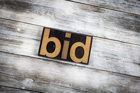 Foto de The word bid written in wooden letterpress type on a white washed old wooden boards background. - Imagen libre de derechos