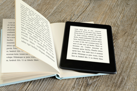 Foto de modern ebook reader on book on wooden table - Imagen libre de derechos