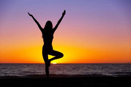 Foto de Silhouette of a beautiful Yoga woman at Sunset - Imagen libre de derechos
