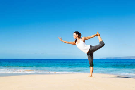 Foto de attractive woman practicing yoga by the beach - Imagen libre de derechos