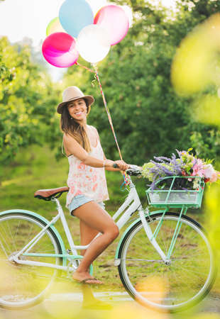 Photo for Beautiful Girl on Bike with Balloons in Countryside, Summer Lifestyle  - Royalty Free Image