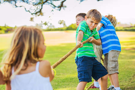 Photo for Group of Happy Young Children Playing Tug oF War Outside on Grass - Royalty Free Image