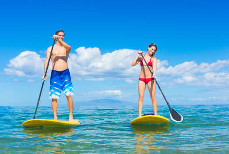 Foto de Couple Stand Up Paddle Surfing In Hawaii, Beautiful Tropical Ocean, Active Beach Lifestyle - Imagen libre de derechos