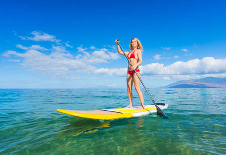 Photo for Attractive Young Woman Stand Up Paddle Surfing In Hawaii, Beautiful Tropical Ocean, Active Beach Lifestyle - Royalty Free Image