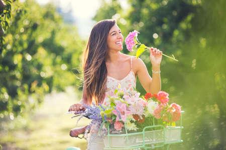 Foto de Beautiful young woman smelling flowers on bike in park - Imagen libre de derechos