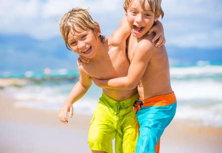 Photo pour Two young boys having fun on tropical beach, happy best friends playing - image libre de droit
