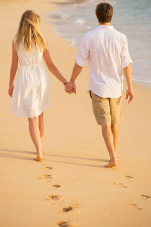 Foto de Romantic couple holding hands walking on beach at sunset. Man and woman in love. Footprints in the sand.  - Imagen libre de derechos