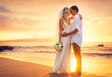Photo pour Bride and Groom, Kissing at Sunset on a Beautiful Tropical Beach, Romantic Married Couple - image libre de droit