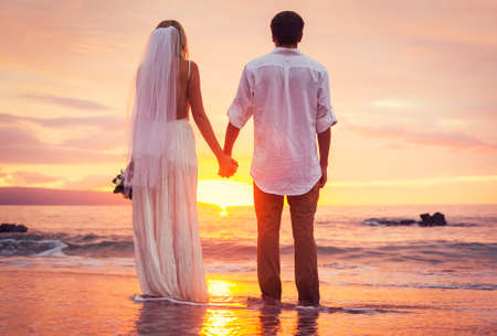 Foto de Bride and Groom, Enjoying Amazing Sunset on a Beautiful Tropical Beach, Romantic Married Couple - Imagen libre de derechos