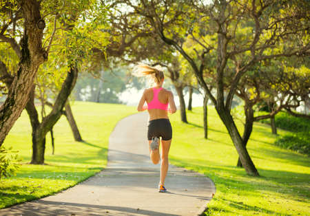 Photo pour Athletic fit young woman jogging running outdoors early morning in park - image libre de droit