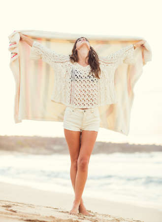 Fashion lifestyle, beautiful young woman on the beach at sunset, warm backlit sunlight