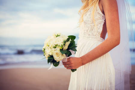 Photo pour Portrait of beautiful bride standing by the beach at sunset - image libre de droit
