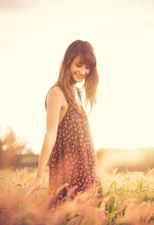 Beautiful young woman outdoors. Romantic Model in Sun Dress in Golden Field at Sunset. Happy Emotions, Glowing Sunlight. Backlit. Warm color tones