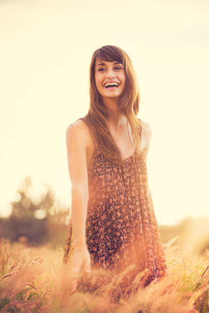 Beautiful young woman outdoors. Romantic Model in Sun Dress in Golden Field at Sunset. Happy Emotions, Laughing. Backlit. Warm color tones