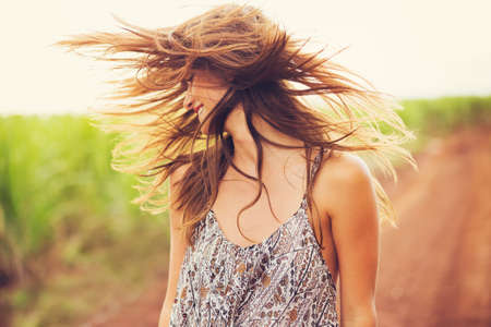 Photo pour Gorgeous Romantic Girl Outdoors. Beautiful  Model in Short Dress in Field. Long Hair Blowing in the Wind. Backlit, Warm Color Tones - image libre de droit