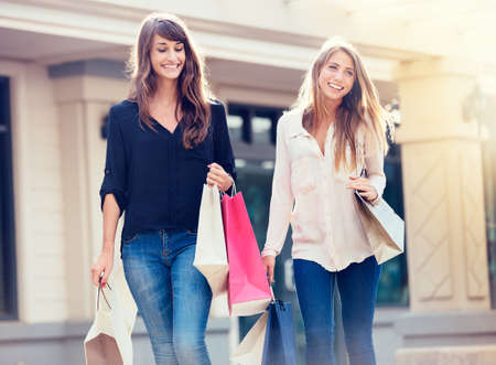 Photo pour Beautiful girls with shopping bags walking at the mall - image libre de droit