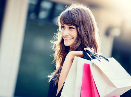 Foto de Happy woman holding shopping bags and smiling at the mall - Imagen libre de derechos