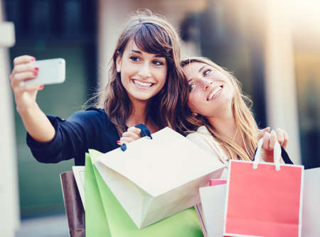 Photo pour Beautiful girls with shopping bags taking a selfie with their cell phone - image libre de droit