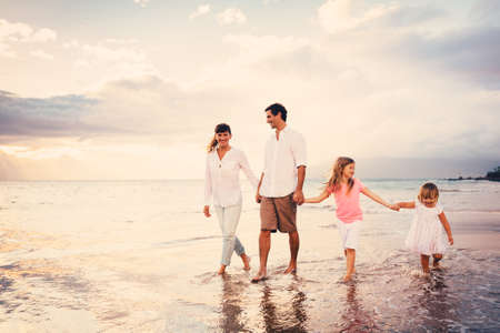 Photo pour Happy Young Family have Fun Walking on Beach at Sunset - image libre de droit
