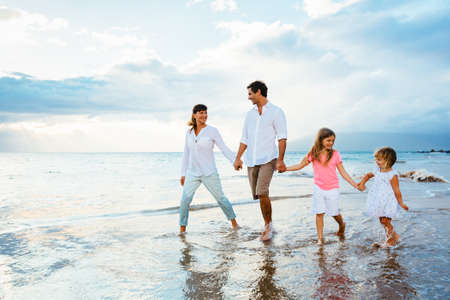 Foto de Happy young family walking on the beach at sunset. Happy Family Lifestyle  - Imagen libre de derechos