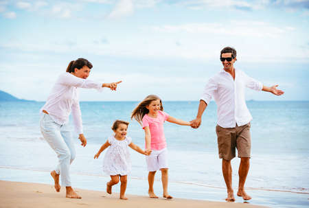 Foto per Happy young family walking on the beach at sunset. Happy Family Lifestyle  - Immagine Royalty Free
