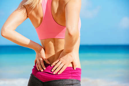 Photo for Back Pain. Athletic fitness woman rubbing the muscles of her lower back. Sports exercising injury. - Royalty Free Image