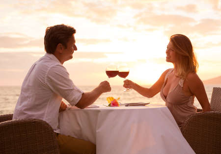 Foto de Couple sharing romantic sunset dinner on the beach - Imagen libre de derechos