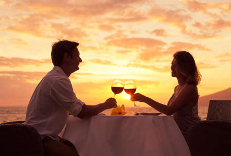 Photo for Couple sharing romantic sunset dinner on the beach - Royalty Free Image