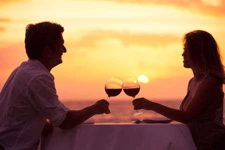 Photo pour Couple sharing romantic sunset dinner on the beach - image libre de droit