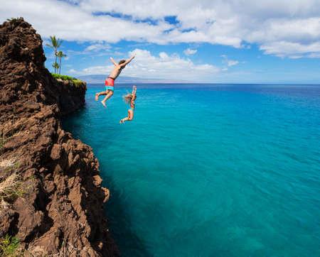 Foto de Summer fun, Friends cliff jumping into the ocean.  - Imagen libre de derechos