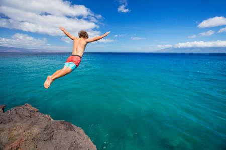 Photo pour Man jumping off cliff into the ocean. Summer fun lifestyle. - image libre de droit