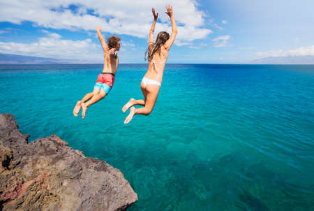 Foto de Friends cliff jumping into the ocean, summer fun lifestyle. - Imagen libre de derechos