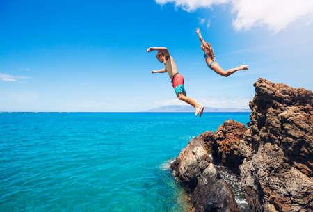 Photo pour Friends cliff jumping into the ocean, summer fun lifestyle. - image libre de droit