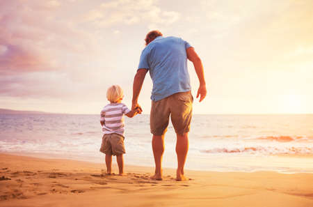 Foto de Father and son standing on the sea shore holding hands at sunset - Imagen libre de derechos