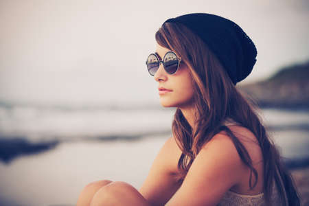 Foto de Fashion portrait of young hipster woman with hat and sunglasses on the beach at sunset, retro style color tones - Imagen libre de derechos
